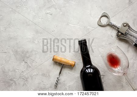 glass bottle of red wine and corkscrew for on white stone background top view mockup