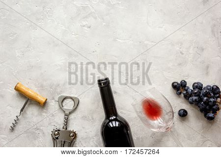 glass bottle of red wine with wineglass on stone texture background top view mock-up