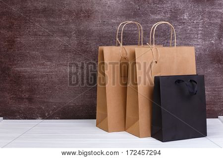 Mockup of blank shopping bags. Brown and black craft packages. Concept for sales or discounts. Recycled paper. Wooden rustic board.