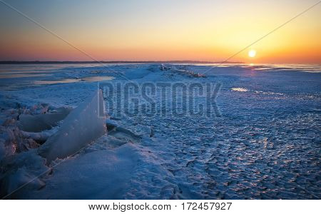 Winter landscape with frozen lake and sunset sky.