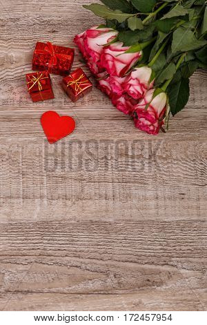 Roses with heart on wood background. Love design. Valentines day or 8 march concept. Fresh natural flowers with gift boxes. Wooden rustic board.