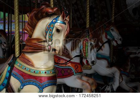 Colorful, ornate carousel horses on poles, with jewels, close up.