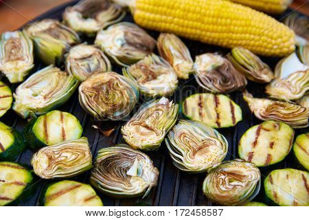 artichoke zucchini and corn cob raw grilled vegetables on steel