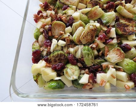 Roasted Brussels sprouts, pecans, cranberries and apples as a side in a glass dish.
