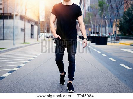 Young muscular man wearing black tshirt and jeans walking on the streets of the modern city. Blurred background. Hotizontal mockup