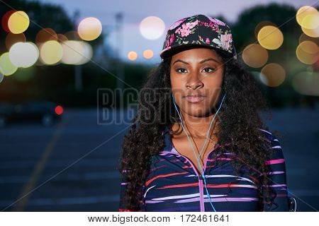 Flash photography portrait of trendy black hipster wearing a cap ready for night jogging in an urban background with bokeh lights