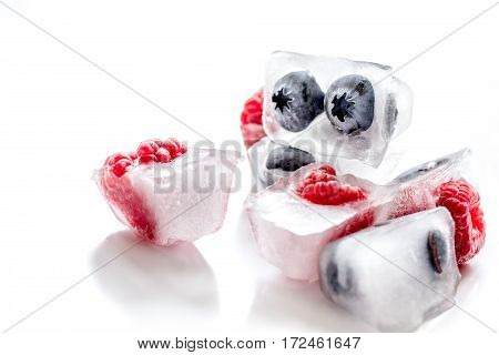 frozen fresh blueberry and raspberry in icecubes on white table background