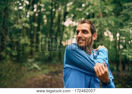 Competitive, athletic young man warms up muscles before running off road outdoors through the woods on a trail in the afternoon wearing sportswear.
