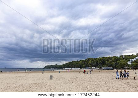 GDYNIA POLAND - JULY 31 2015: People walking on Municipal beach in Gdynia city Baltic sea Poland. Cloudy summer day