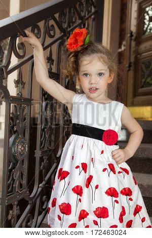 little girl in a dress on a background of the stairs