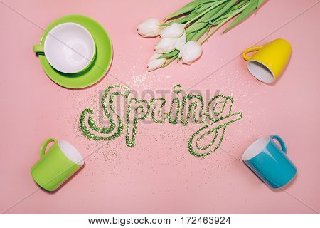 Word SPRING made of greenery glitter. White tulips and many colorful cups on pink background. Spring coming concept. Pop-art style picture, flat lay.
