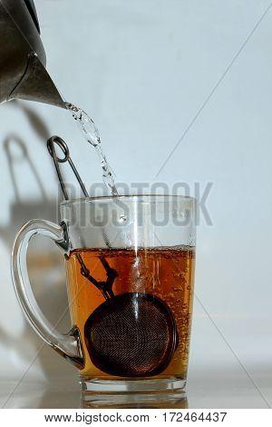 Metal tea infuser in a glass tea cup