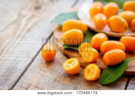 kumquat on plate at wooden table close up