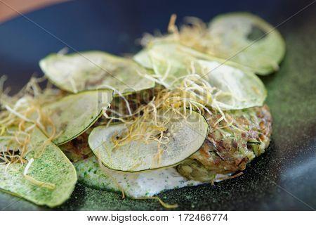Creative gourmet vegetarian appetizer - zucchini fritters on black porcelain plate