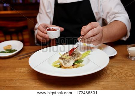 Chef is adding tomato sauce to a fish dish