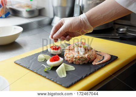 Chef is decorating crab salad in restaurant kitchen