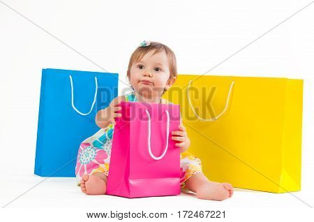 Little girl sitting with colorful paper bags isolated on white background