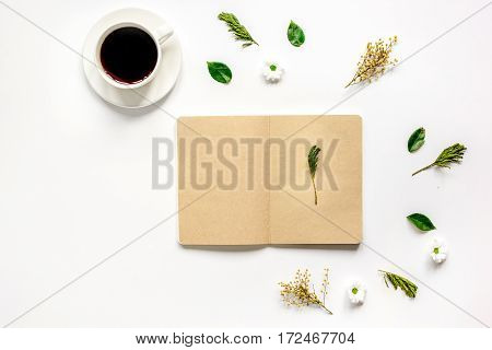 Flower petals, cup of coffee and brown craftpaper copybook on table background top view mock up