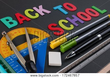Mathematical Instruments Over The Corner Of Black Paper With Text Back To School. Back To School Wit