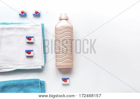 Bright towels pile with washing powder in laudry set on white table background top view mock-up