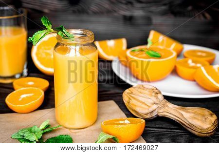 Cut fresh oranges with homemade juice in bottle and mint leaves on kitchen background