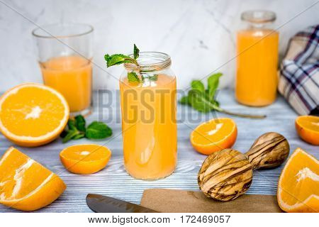 homemade healthy fresh orange cocktail with mint leaves for lunch in bottle on kitchen background