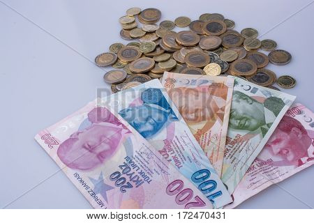 Turkish Lira coins and banknotes side by side on white background