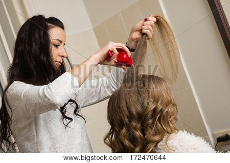 Barber makes a girl hairstyle at the beauty salon.