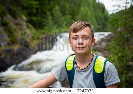 Boy tourist with a backpack standing near the mountain waterfall.