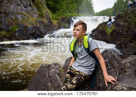 Portrait of a teenage boy standing near a waterfall in the summer