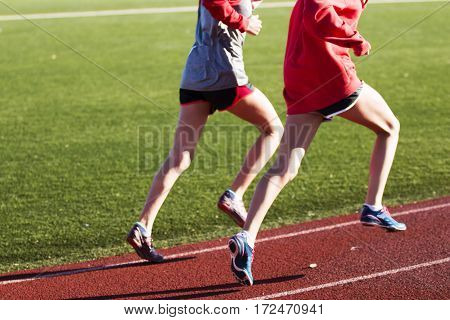 Two girls training for speed together on a red track