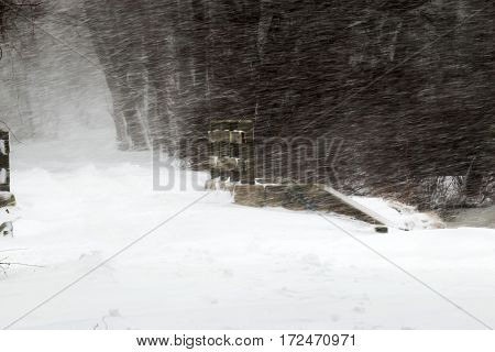 Snow storm in Southards Pond showing the snow blowing sideways over a wooden bridge