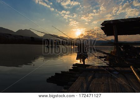 Shooting backlit atmosphere morning of fishing fishing rods leaning on bamboo while the sunrise. On the floating house Khao Leam national park Sangkhlaburi Kanchanaburi Thailand.