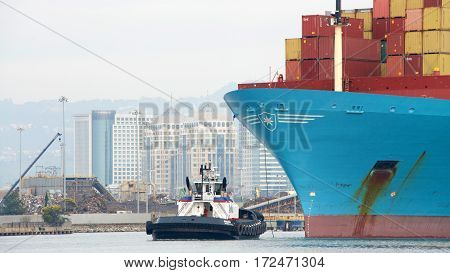 Oakland CA - January 31 2017: Tugboat REVOLUTION at the bow of cargo ship GEORG MAERSK assisting the vessel to maneuver into the Port of Oakland.