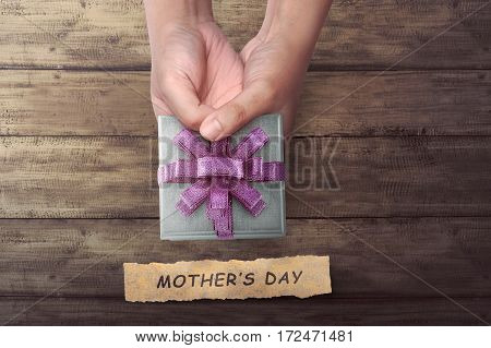 People Hand Holding Small Gift With Mother's Day Greeting