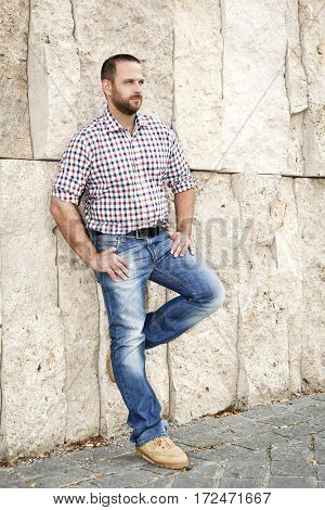 An image of a handsome man with a beard at the wall