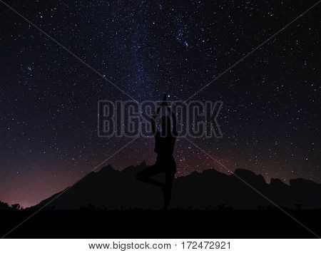 Silhouette young woman practicing yoga pose at night under sky full of stars with colorful milky way