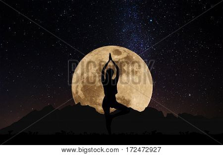 Silhouette young woman practicing yoga pose at night under full moon with sky full of stars