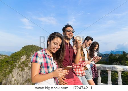 Young People Group In Mountain Using Cell Smart Phone Chatting Online Friends Asian Holiday Summer Vacation Travel