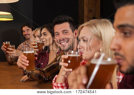 Young People Group In Bar, Friends Sitting At Wooden Counter Pub, Drink Beer Communication Party Celebration