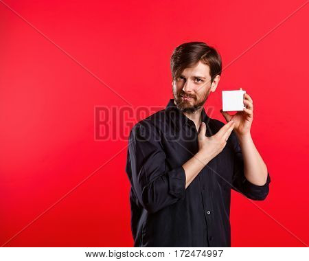 Man holding an empty cube. Advertising Space. Attractive man shows space for copy. Noteworthy.