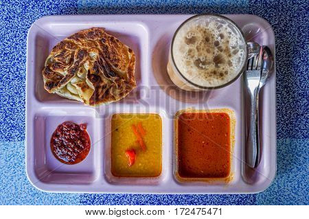 Famous Malaysian breakfast,Roti Bom or Flat bread,teh tarik or milk tea & curry.Roti Bom is a variant of Roti Canai.It is thicker and sweeter and served with condensed milk and sugar. A type of bread with Indian influence available in Malaysia and Singapo