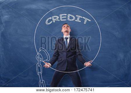Businessman on blue chalkboard background lifting a big iron ball drawn in white with a word 'Credit'. Business and finance. Banking and investment. Business expenses.