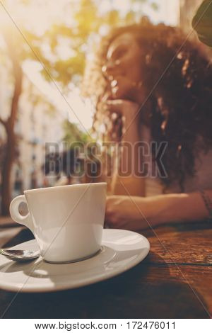 Vertical shoot of white cup and saucer with coffee and laughing brunette hipster girl in background cup of tea on the table with blurred curly smiling woman waiting until her drink will be cooled