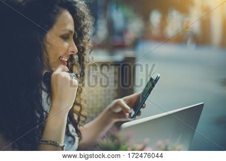 Pensive beautiful white caucasian girl with black curly hair sitting in street bar and texting message to her boss happy freelancer woman browsing site on her smart phone with opened laptop in cafe