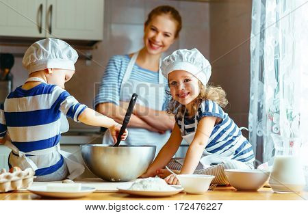 happy family in the kitchen. mother and children preparing the dough bake cookies