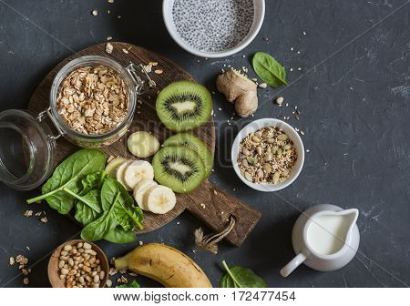 Ingredients for a healthy breakfast - chia pudding oatmeal banana kiwi spinach coconut milk on a dark background top view. Flat lay