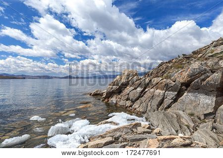 Landscape with textured rock, white clouds and white melting ice along coastline in spring day
