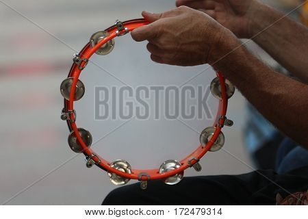 Colorful tambourine being played  in musical hands