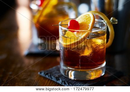 tasty alcoholic old fashioned cocktail with orange slice, cherry, and lemon peel garnish